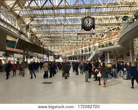 LONDON - FEBRUARY 17, 2017: Passengers under the concourse clock inside London Waterloo Railway Station in Waterloo, Lambeth, London, UK. Local and suburban services are operated by South West Trains.