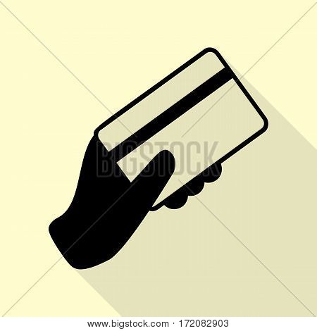 Hand holding a credit card. Black icon with flat style shadow path on cream background.