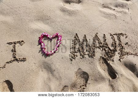 I LOVE Maui. the words I love maui written in sand on the beach with a Hawaiian lei for the heart symbol of love.