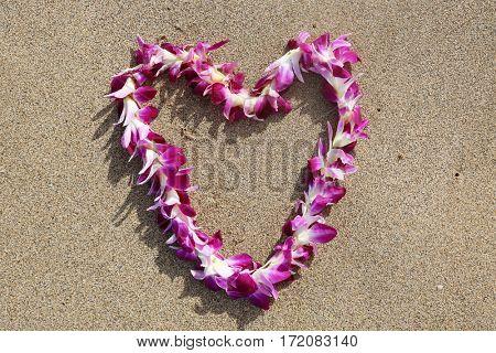 Hawaiian lei. Hawaiian lei on sand on the beach in a heart shaped designs.
