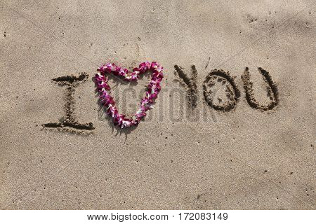 I LOVE You. the words I love you written in sand on the beach with a Hawaiian lei for the heart symbol of love.