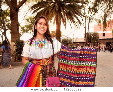 ANTIGUA, GUATEMALA-DEC 26, 2015: : Beautiful guatamalian girl selling traditional colorful fabric at the street in Antigua on Dec 26, 2015, Guatemala.