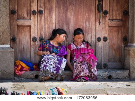 ANTIGUA, GUATEMALA-DEC 26, 2015: : Guatamalian girls selling traditional  colorful fabric and goods at the street in Antigua, on Dec 26, 2015, Guatemala.