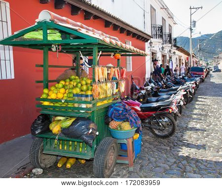 ANTIGUA, GUATEMALA-DEC 27, 2015: Mayan man sells  fruit at the street of Antigua on Dec 27 2015. Guatemala.