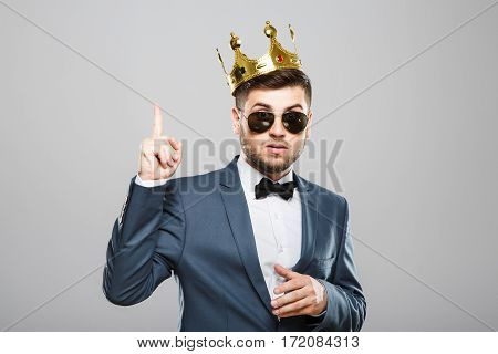 Stylish young man in suit with bow and sunglasses. Wearing crown. Having idea, finger raised, surprised. Outrageous, fancy look. Waist up, studio, indoors