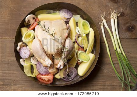 Preparation for roasting chicken with herbs and vegetables in a copper pot