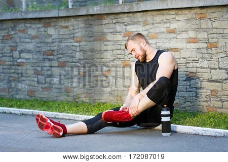 Pain in leg, sport injury. Man sitting and holding his leg. Sportsman limbering up leg, bottle with water standing next to him. Full body, outdoors