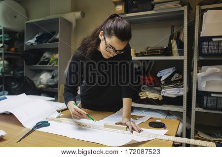 female fashion desighner draws dress template on panel table in workshop interior