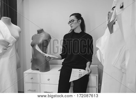 young female fashion designer view on fashion sketches near mannequin monochrome photo