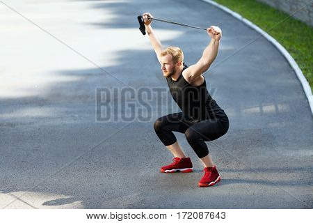 Profile of man training with expander. Muscular sportsman squatting with expander, hands up. Sport, outdoors, stadium, full body, horizontal