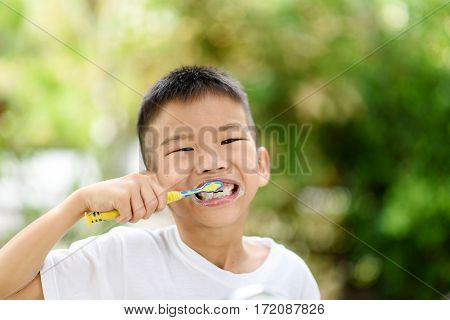 Boy Brushing Teeth In The Garden