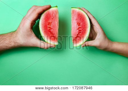 Slices of Mini Watermelon in Female and Male Hands with Green Copy Space. Relationship Concept.