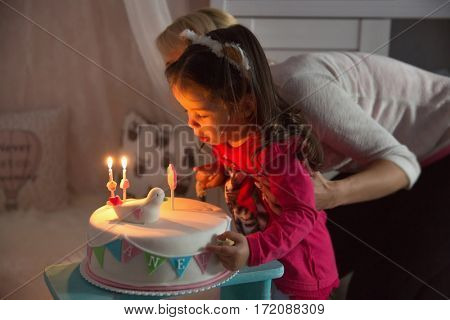 Little girl celebrating her second birthday and blowing on candles for his birthday cake