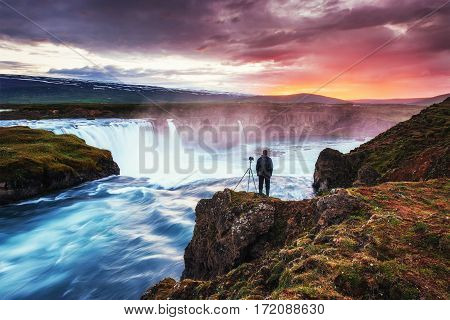 Beautiful Icelandic waterfall Hodafoss. It is located in the north near Lake Myvatn and the Ring Road. Fantastic landscape. Beautiful cumulus clouds. Man considers beauty