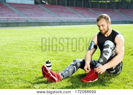 Man sitting on grass and tightening lacings of red sneakers. Sportsman resting on stadium, bottle with water standing next to him. Full body, outdoors, stadium