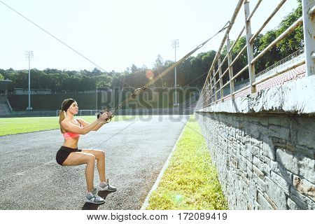 Sport, exercises with training loop outdoors. Profile of sporty girl in rose top and black shorts squatting with training loop on stadium. Full body, profile, outdoors