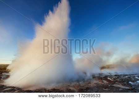 Strokkur geyser eruption in Iceland. Fantastic colors. Beautiful pink clouds in a blue sky.