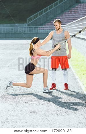 Sport, exercises with training loop outdoors. Girl in rose top and black shorts doing exercises with training loop on stadium. Coach making corrections, helping with exercises. Profile, fullbody