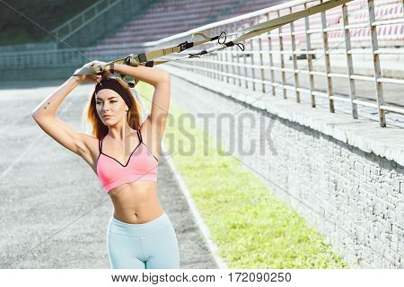 Sport, exercises with training loop outdoors. Girl in rose top and blue leggins doing exercises with training loop on stadium. Sporty girl in good shape with hands up, looking aside, closeup