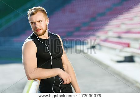 Man taking stop after running on track, looking aside. Sportsman in black training suit standing near tribune of stadium. Outdoors, stadium, sunlight, unfocused background