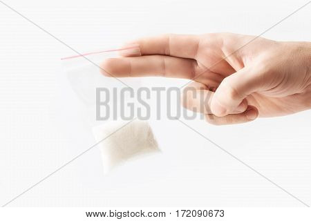 Hand holding Plastic transparent zipper bag with half Granulated sugar isolated on white, Vacuum package mockup with red clip. Concept
