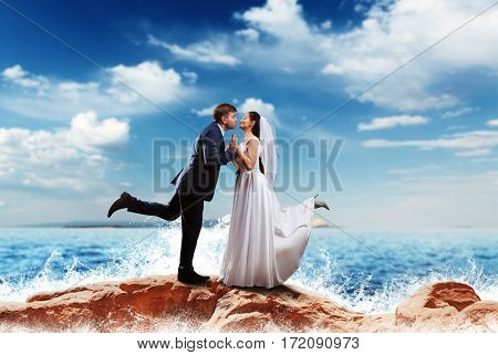 Bride and groom kissing on the sea shore