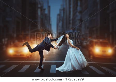 Newlyweds crossing a night city street