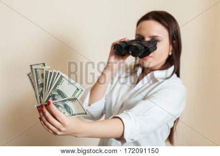 Woman looks through binoculars on money fan