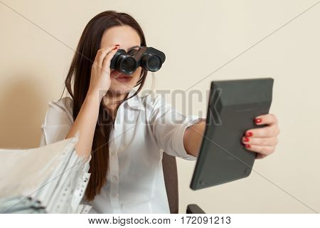 Bookkeeper looks through binoculars on calculator