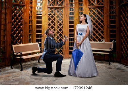 Groom proposing to the bride in a wooden gazebo