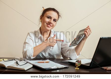 Happy young female accountant with calculator