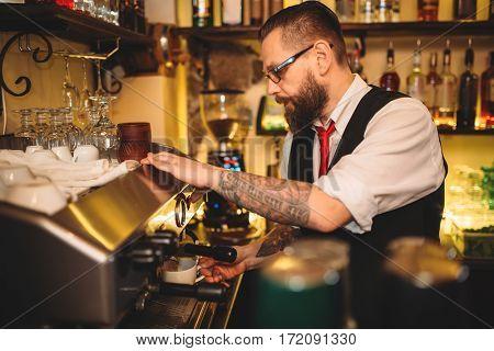 Barista preparing coffee in espresso machine