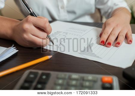 Bookkeeper signs accounting balance sheet