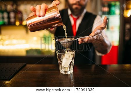 Barman flaring behind bar counter