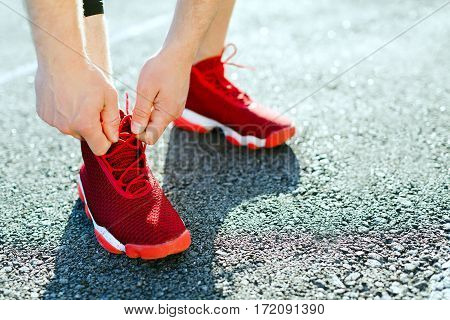 Sport concept, red sneakers for running. Man tightening lacings on his sneakers, no face. Legs in professional sport shoes, closeup. Outdoors, sunlight, stadium