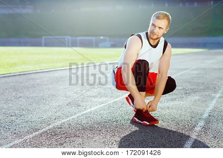 Man crouched in red sneakers for running. Man tightening lacings on his sneakers and looking aside. Sportsman on stadium before running. Outdoors, sunlight, stadium