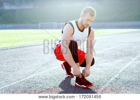 Man crouched in red sneakers for running. Man tightening lacings on his sneakers. Profile of sportsman on stadium before running. Outdoors, sunlight, stadium