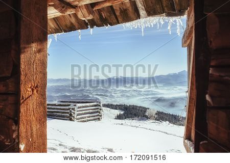 Cabin in the mountains in winter. Mysterious fog. In anticipation of holidays. Carpathians. Ukraine, Europe