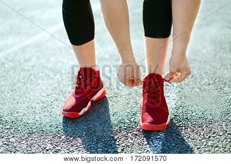 Sport concept, red sneakers for running. Man tightening lacings on his sneakers, no face. Legs in sport shoes. Outdoors, sunlight, stadium