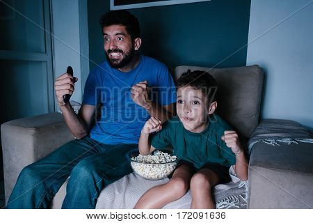 Father and son watching TV and cheering at night