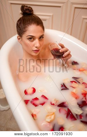 Woman holding a glass of red wine in bath