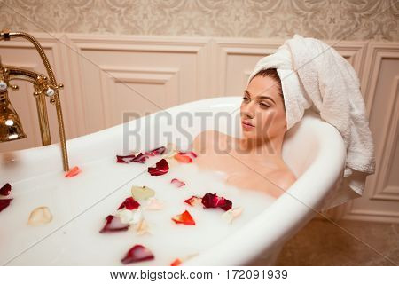 Woman in bathroom with rose petals