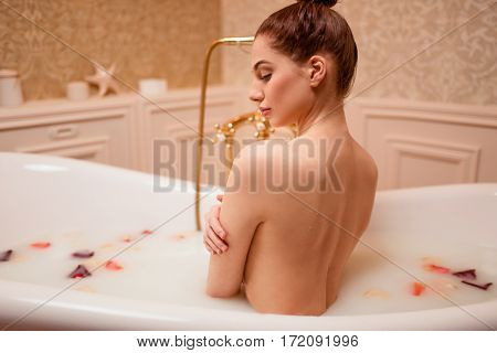 Woman in bathtub with rose petals and foam