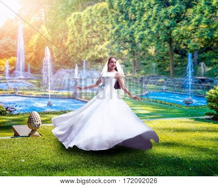Young bride in green park with fountains
