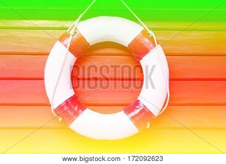 Lifebuoy hanging on wood wall with color filters