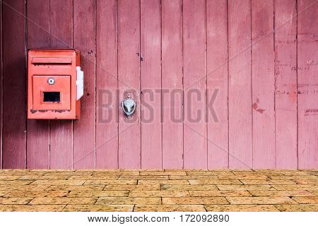 Red mailbox on the red wooden door with brick wall