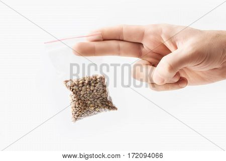 Hand holding Plastic transparent zipper bag with half lentils beans isolated on white, Vacuum package mockup with red clip. Concept