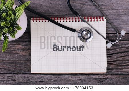Burnout Word On Notebook,stethoscope And Green Plant.