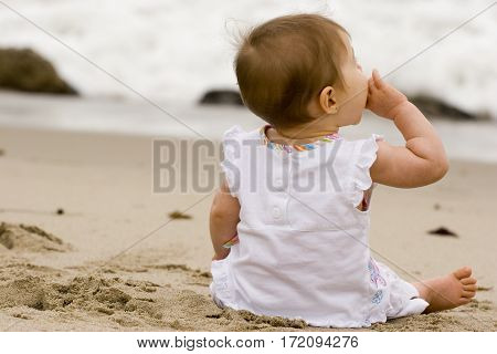 Cute little girl playing in the sand on the beach.