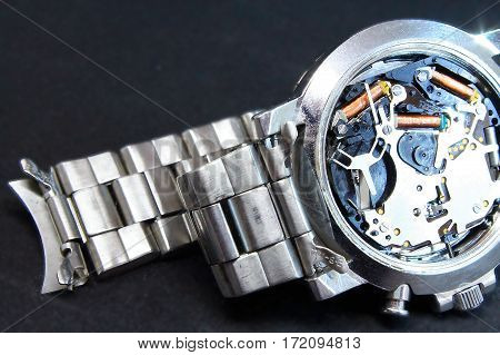 Silver watch with case back removed for sizing and repair.
